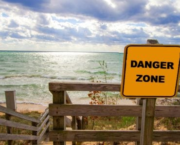 Rip Current Warning. Sign at beach entrance warning of dangerous rip currents as waves crash on to the coast of Lake Michigan. - Image(ehrlif)s