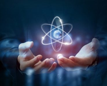 Hands shows the atom on a dark blurred background. - Image( Natali_ Mis)s