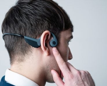 Young man wearing a bone conduction headphones(metamorworks)S