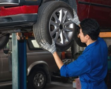 Asian mechanic checking wheel under the car to repair(ReeAod)s
