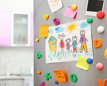 Sheets of paper, child's drawing and magnets on refrigerator door in kitchen( New Africa)s