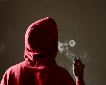 blows a single smoke ring while holding an electronic cigarette in hand(Chicken Strip)S