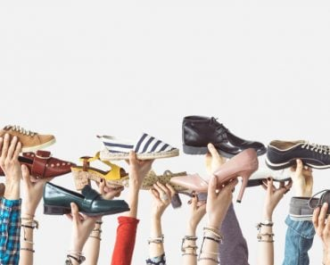 Hands holding different shoes on isolated background(sebra)s