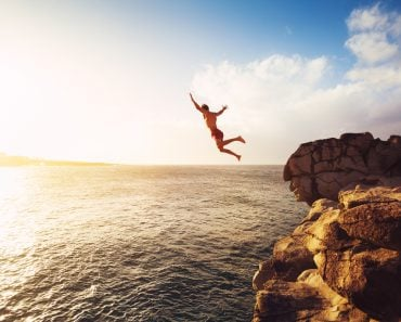 Cliff Jumping into the Ocean at Sunset(EpicStockMedia)S