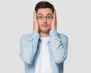 Funny worried man in glasses jean shirt hold head in hands looks concerned pose studio grey wall(fizkes)S
