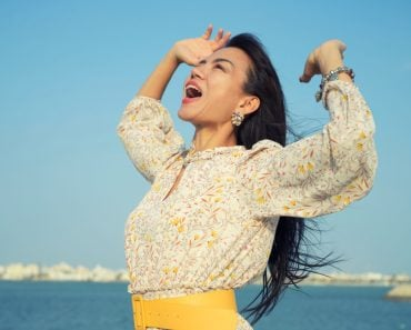 Beautiful Asain woman yelling to sky with hands open in the air over blue sea(Jantira Namwong)s