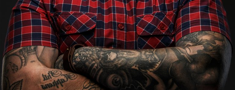 Portraite of brutal hipster with tattooes on his hand dressed in red shirt and bow tie(FXQuadro)S