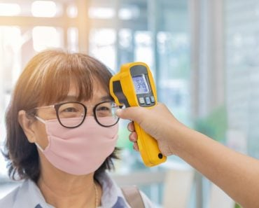 Security guard using digital medical electronic thermometer measures checking body temperature screening passengers(Soonthorn Wongsaita)s