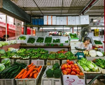 One elderly woman working at a greengrocery store inside the wet market in Chinatown, Singapore(Filipe.Lopes)s