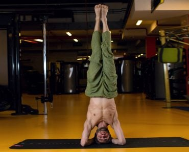 Shirshasana pose. A man practising yoga doing a headstand