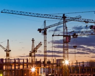 Silhouettes of tower cranes against the evening sky. House under construction. Industrial skyline(Oleg Totskyi)s