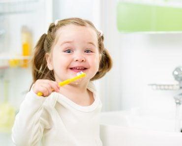 smiling kid girl brushing teeth in bathroom(Oksana Kuzmina)s