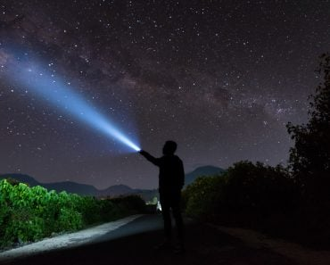 An amazing milky way and stargazing with a silhouette man flashing the light towards the stars(yusuf madi)S