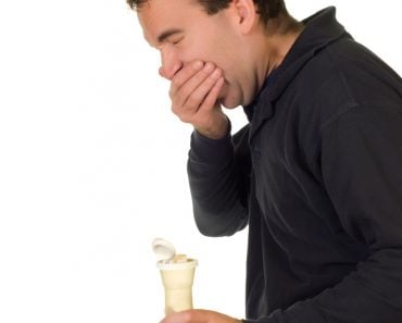 A man holding a pepper shaker and sneezing(dragon_fang)s