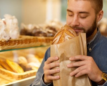 Close up of a young bearded man smelling delicious freshly baked bread at the bakery store(Zoriana Zaitseva)S
