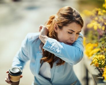 A young businesswoman on a coffee break outside is sneezing into the elbow by an allergy or a cold(MilanMarkovic78)s