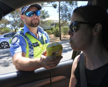 Australian traffic police officer using breathalyzer on woman driver during field sobriety testing(ChameleonsEye)s