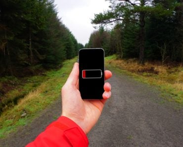 A person holding a phone in their hand with dead battery(Timothy Dry)s