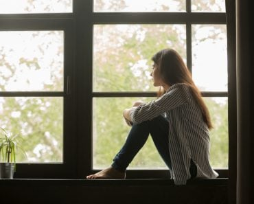 Thoughtful girl sitting on sill embracing knees looking at window(fizkes)s