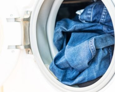 Open door in washing machine with jeans inside close up(Tommy Lee Walker)S