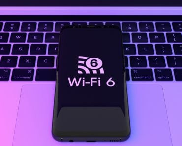 Wi,Fi,6,Logo,On,Smartphone,With,Laptop,Background.,Wi