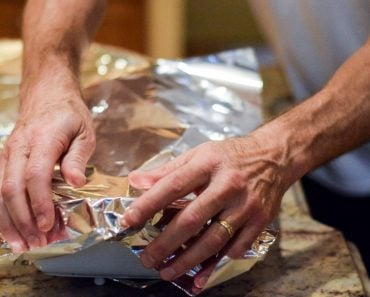 Hands covering casserole dish with aluminum foil to back in oven(Cabeca de Marmore)S
