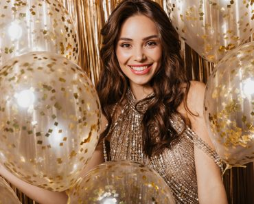 Smiling lady in shining top looking at camera among balloons with golden confetti
