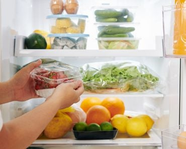 Hands of woman opening fridge door and putting package of fresh ripe strawberries in it