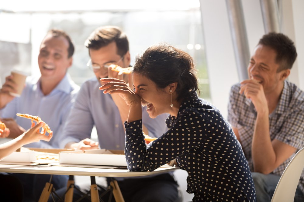 Indian woman laughing at funny joke eating pizza with diverse coworkers in office(fizkes)S