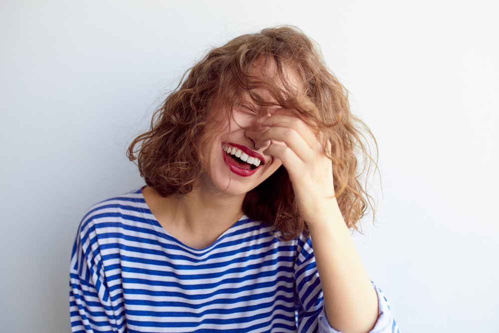 Laughing woman in marine shirt with curly hair over white wall(Mark Nazh)S