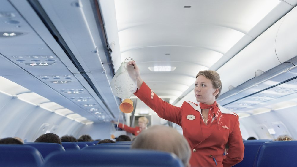 air hostess demonstrating the use of an oxygen mask