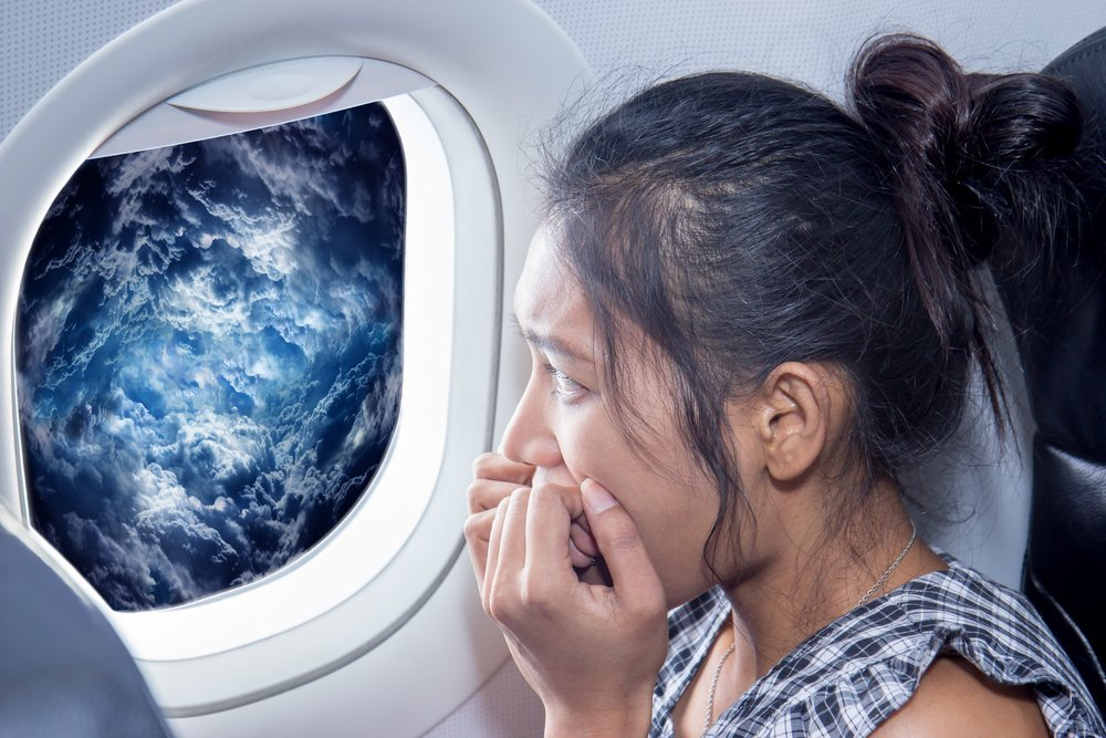 Scared woman looks at the clouds from an air plane window Traveler looking out the airplane window on a raging storm. Passenger has a fear of plane crash. Woman on the aircraft looking at storm clouds.