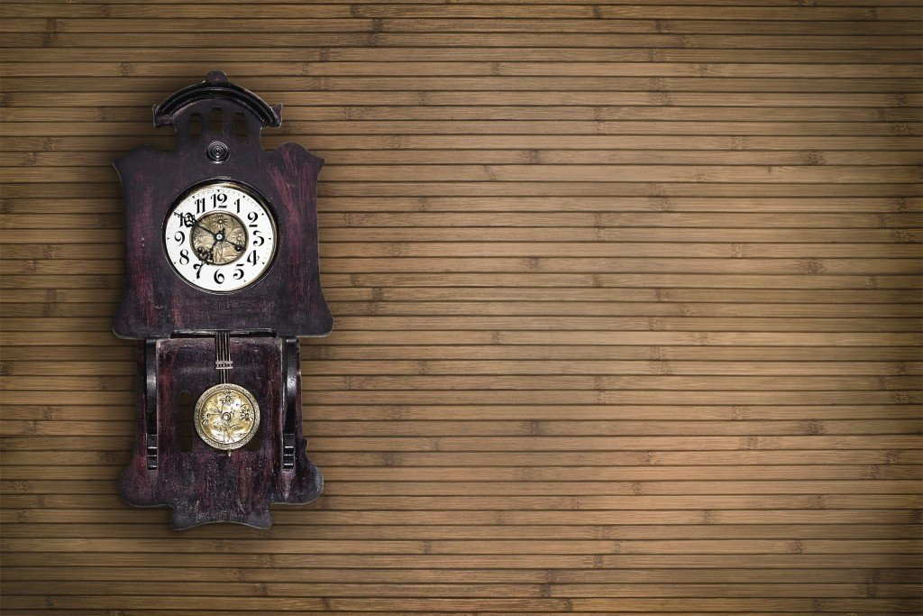Old pendulum clock on the background of wooden wall