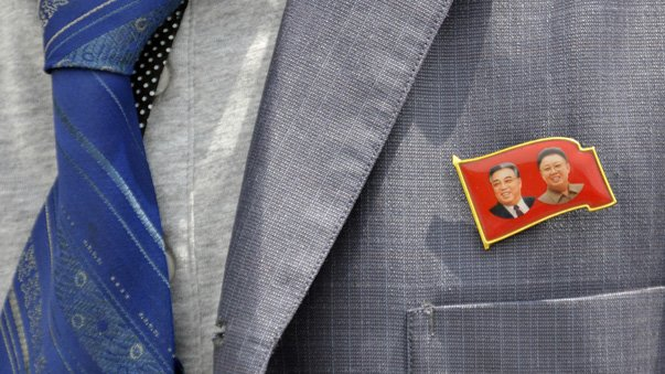 A participant wears a badge showing former North Korean leaders Kim Il Sung and Kim Jong Il during the opening ceremony of a new dock at the port of Rajin July 18, 2014. The dock was jointly built with Russia after last year's completion of a railway link to North Korea, holding out the prospect of increased trade for the reclusive nation with its biggest neighbours after years of international sanctions. Picture taken July 18, 2014. REUTERS/Yuri Maltsev