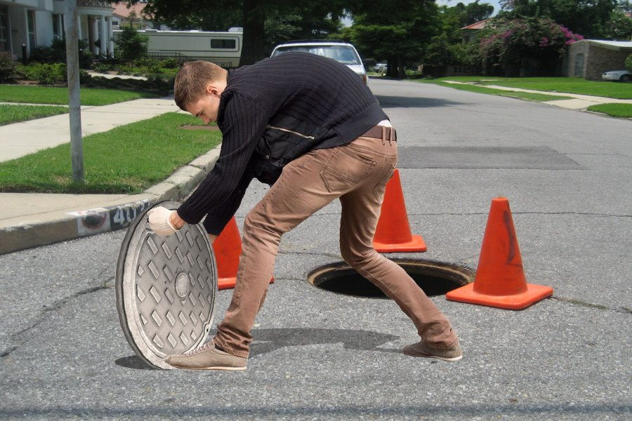 man-moving-manhole-cover