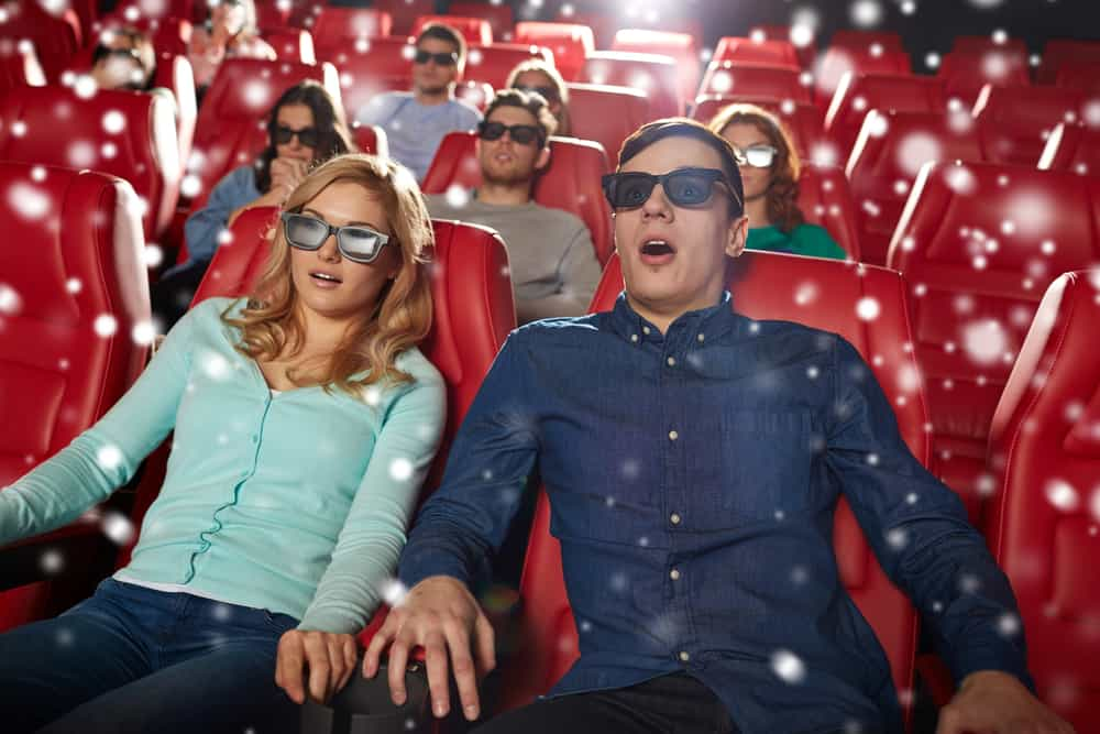 cinema, technology, entertainment and people concept - scared friends or couple with 3d glasses watching horror or thriller movie in theater with snowflakes Watching a scary movie