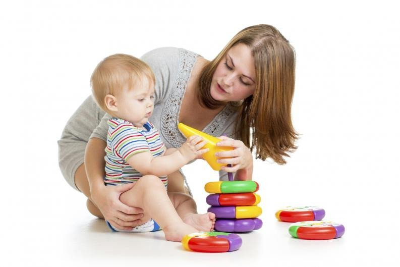 baby boy and mother playing together with construction set toy handing toy to mother