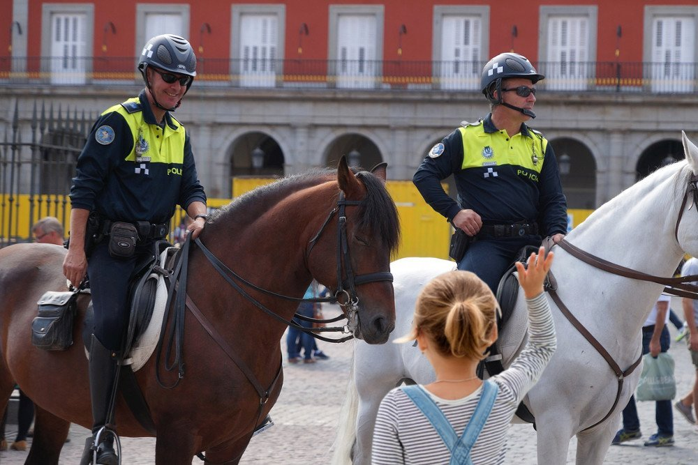 Mounted police officer smilling on little girl