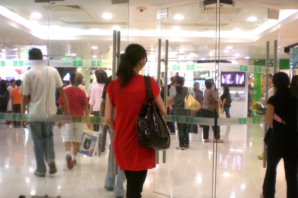 Woman entering in the shopping mall entrance
