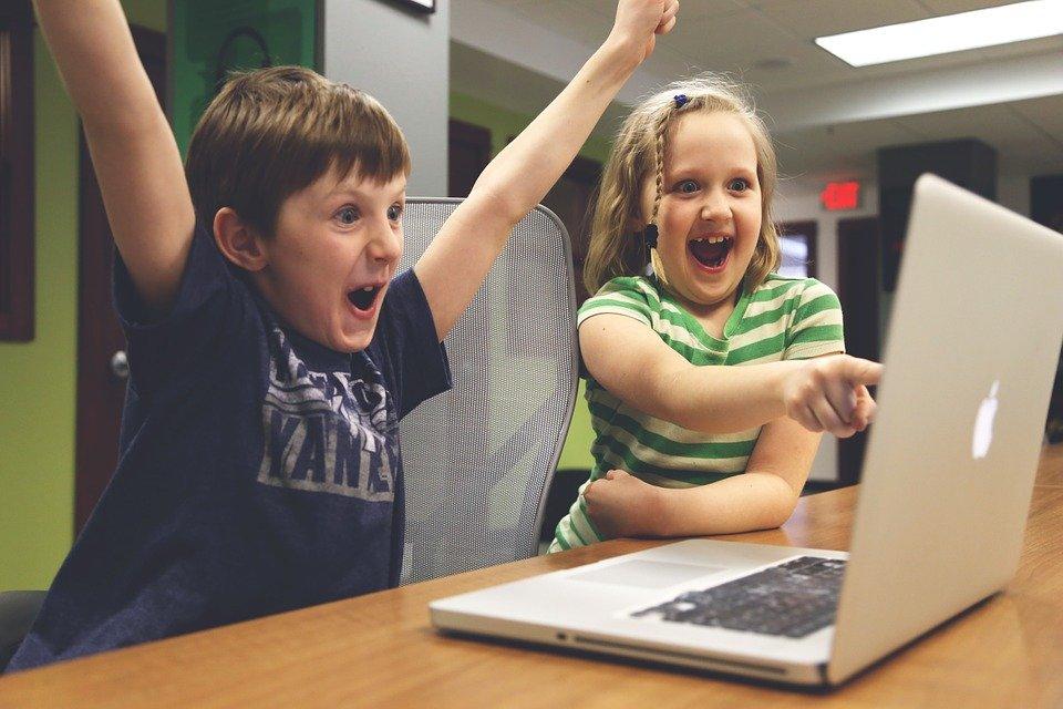 children playing video game computer laptop
