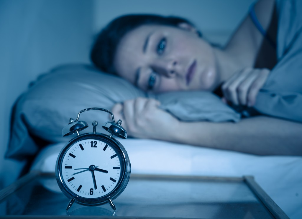 Sleepless and desperate beautiful caucasian woman awake at night not able to sleep, feeling frustrated and worried looking at clock suffering from insomnia in sleep disorder concept. - Image
