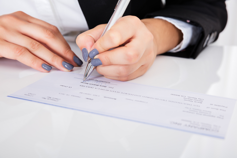 Close-up Of Person's Hand Signing Cheque On Desk - Image( Andrey_Popov)s
