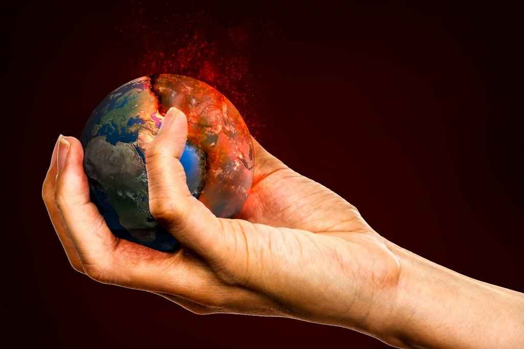 Ecology concept, holding the Earth in hands destroying it Elements of this image furnished by NASA Image (Adisorn Saovadee)
