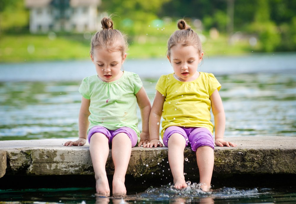 Identical twins girls are exercising on lake shore, sprinkling water. Children sitting on lake side, playing with water. Healthy and active children lifestyle. - Image(JGA)s