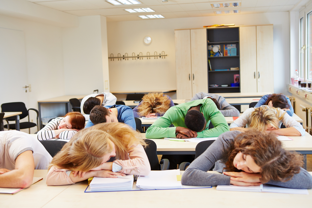 Many tired students sleeping in classroom with their heads on the table - Image( Robert Kneschke)s