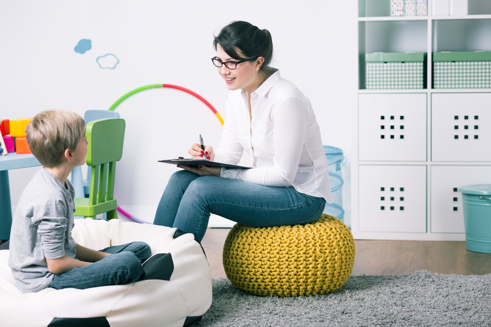 Shot of a young child psychologist talking with a boy - Image( Photographee.eu)S