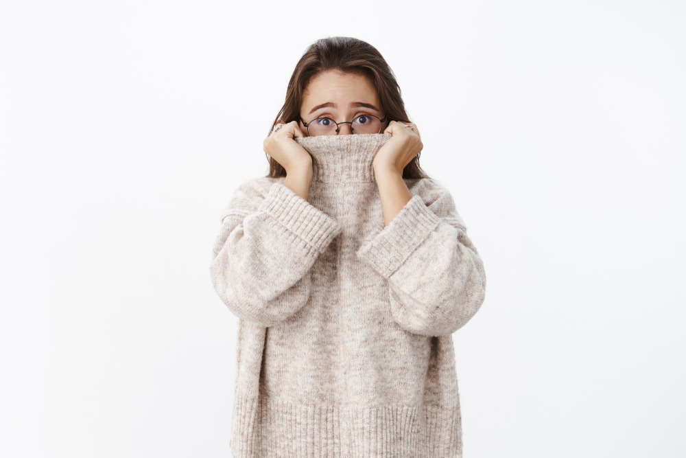 Indoor shot of insecure worried young cute woman in glasses with brown hair pulling collar of sweater on nose and frowning nervously as looking scared at camera, posing anxious over gray background - Image( Cookie Studio)s