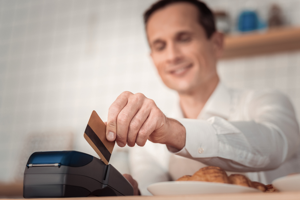 Financial operation. Selective focus of a credit card being in use by a nice joyful man while making non cash payment - Image( YAKOBCHUK VIACHESLAV)s