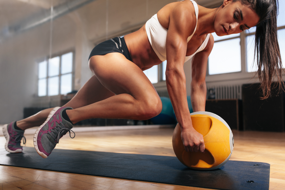 Muscular woman doing intense core workout in gy( Jacob Lund)S