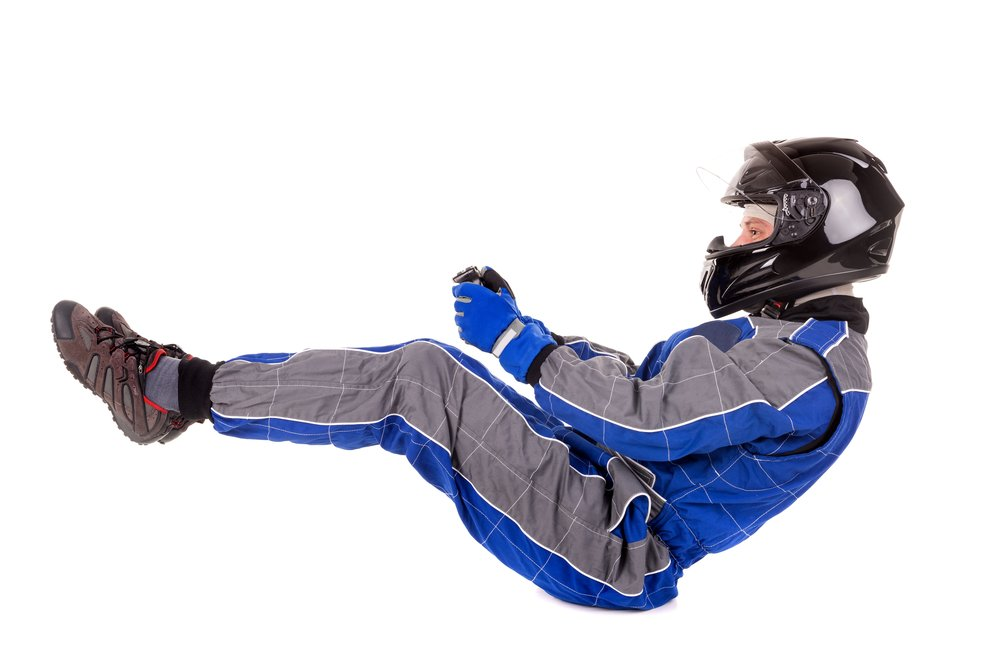 Racing driver posing in driving position in full gear isolated in white(Luis Louro)s